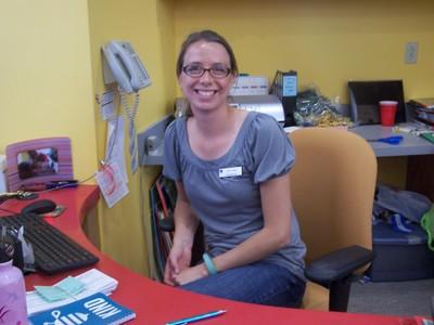 woman in blue shirt behind a desk