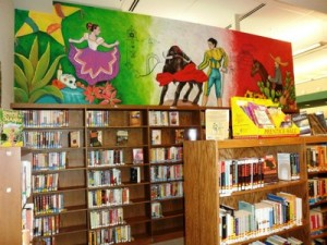 mural of Mexican dancer and bullfighter above bookshelves