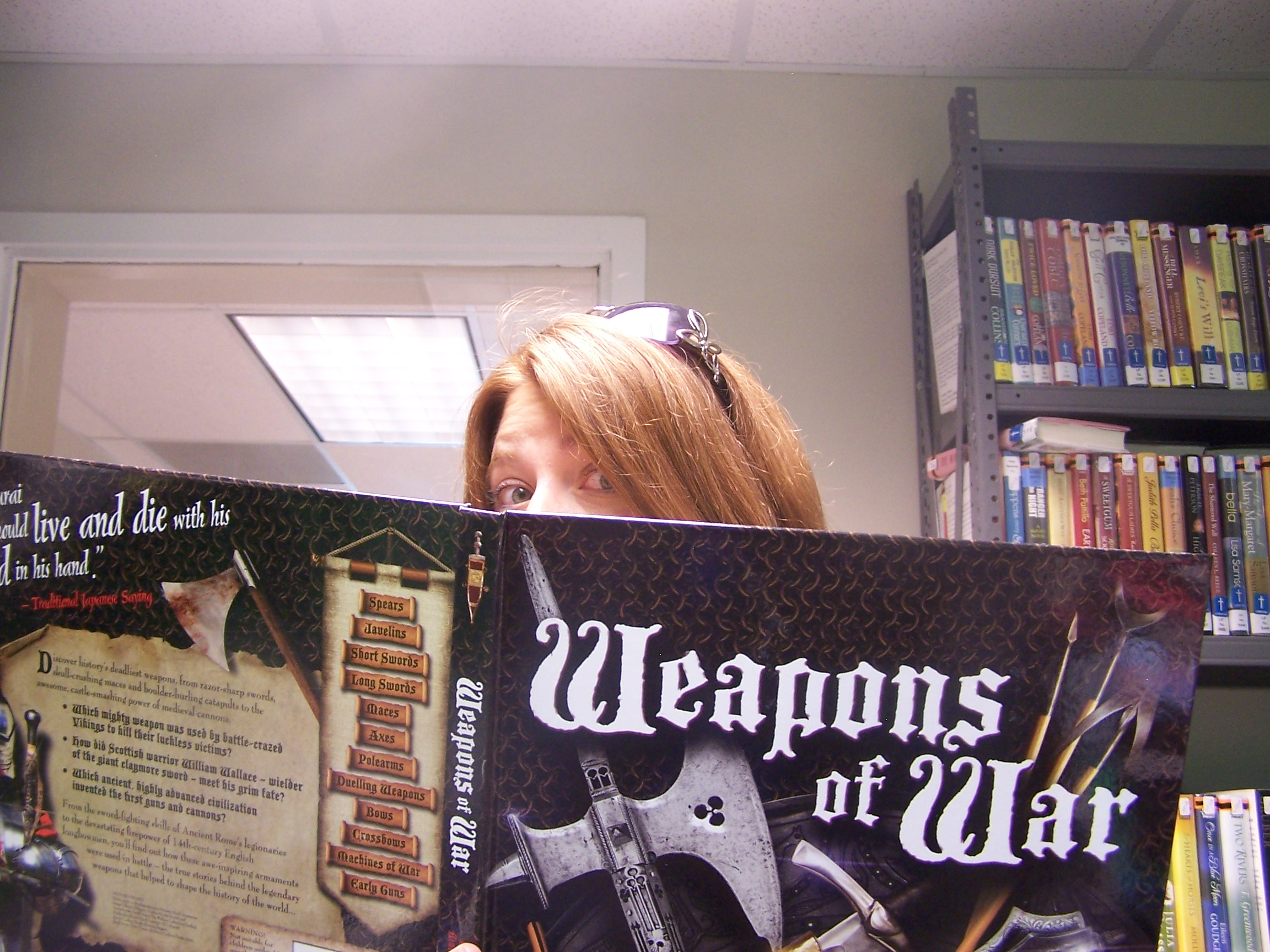 woman peeking out from behind book titled Weapons of War