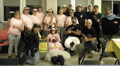 group of people posing for photo; some in pink t-shirts, some in black